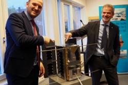 Samferdselsminister Jon Georg Dale (til venstre) og Christian Hauglie-Hanssen, administrerende direktør ved Norsk Romsenter, viser frem en modell av den norske satellitten NorSat-1. Foto: Norsk Romsenter