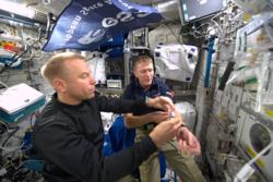 Den amerikanske astronauten Tim Kopra (t.v.) en blodprøve av sin britiske kollega Tim Peake på den internasjonale romstasjonen i 2015. Foto: ESA/NASA