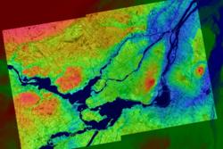 Montreal i Canada sett av Radarsat-1. Bildet er et mosaikkbilde med kunstige farger. Bykjernen sees i midten av bildet, med jordbruksland rundt. Foto: CSA