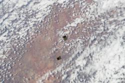 Cubesatellitter i bane høyt over jorda like etter at de har blitt satt fri fra romstasjonen i november 2013. Foto: NASA