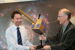 Bjørn Ottar Elseth (t.v.) ved Norsk Romsenters overrekkes en modell av AISSat-1 av Bjørn T. Narheim ved FFI. Foto: NRS
