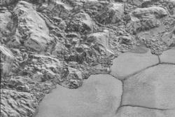 """Fjell, """"kystlinje"""" og enorme flater av is på Pluto, sett av romsonden New Horizons. Dette er detalj av den hjerteformete sletten Sputnik Planum. Foto: NASA/JHUAPL/SwRI"""