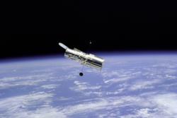 Romteleskopet Hubble med jorda i bakgrunnen. Foto: NASA