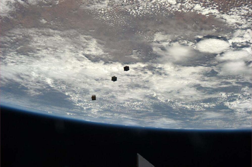 Cubesatellitter svever over jorda etter å ha bli satt fri fra den internasjonale romstasjonen i november 2013. Foto: NASA