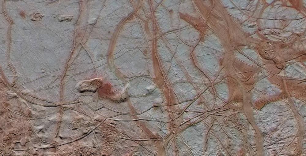 Nærbilde av stripene og sprekkene i isen på Jupiters måne Europa. Her spruter geysirer ut flytende vann fra havet under isen. Foto: NASA/JPL