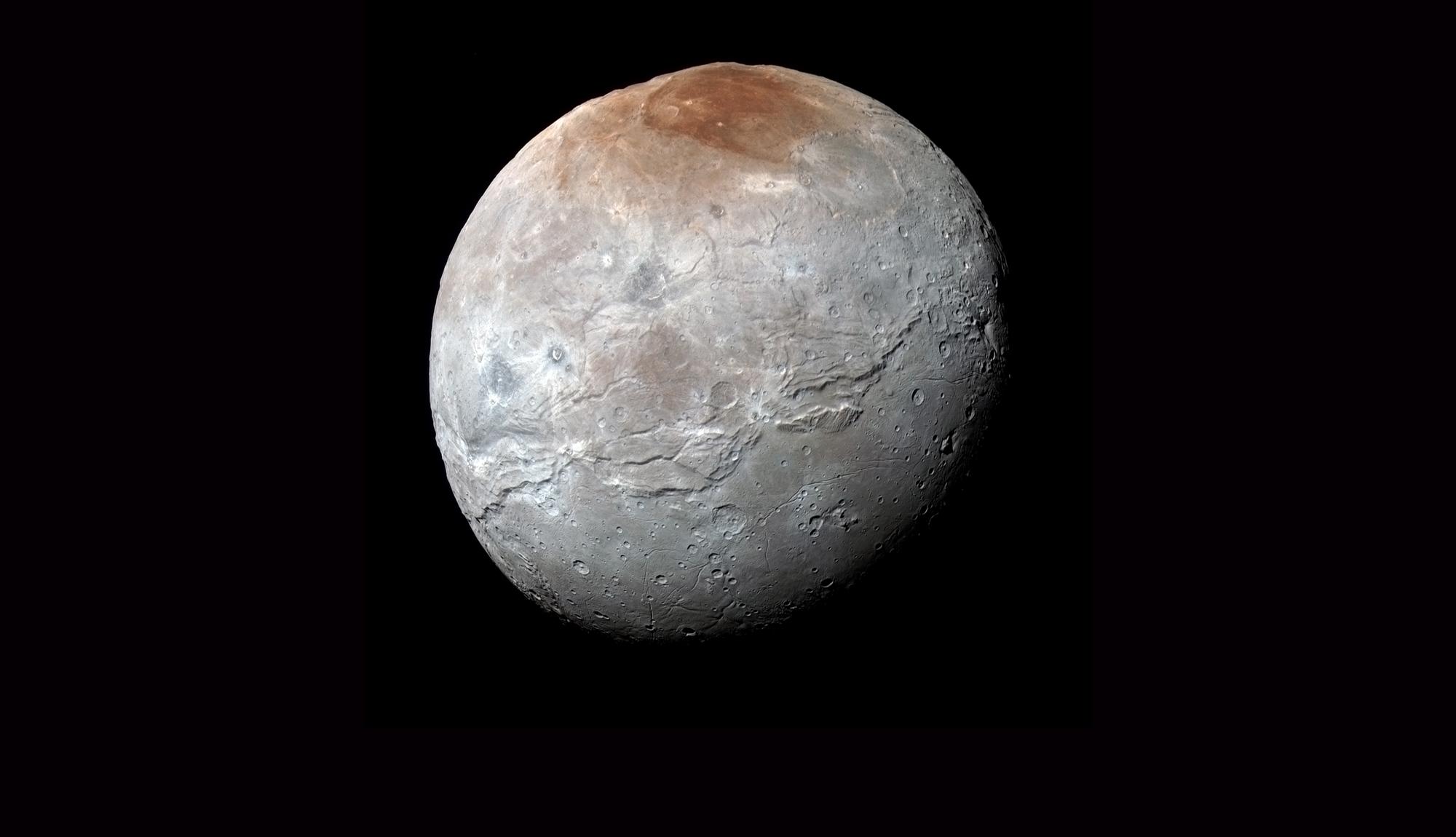 Plutos måne Charon sett av New Horizons i juli 2015. Det røde nordpolområdet kalles Mordor Macula, slettene i sør Vulcan Planum. Kløften langs ekvator er solsystemets nest lengste. Foto: NASA/Johns Hopkins University Applied Physics Laboratory/Southwest Research Institute