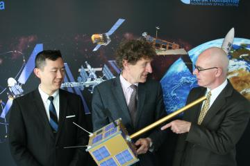 The Canadian Ambassador to Norway, David Sproule (far right), is looking at a model of AISSat-1, the first satellite platform built by UTIAS for the Norwegian state. He is flanked by Bo Andersen (middle) and Dr. Robert E. Zee.